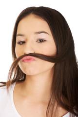Teen woman putting hair like moustache.