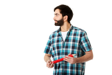 Young man holding big red pencil.