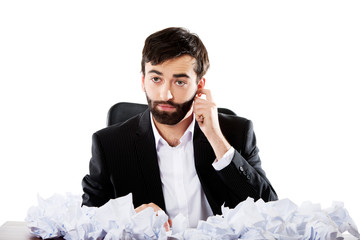 Young businessman sitting with crushed sheets.