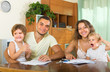 Parents and little daughters with documents