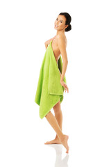 Side view woman standing wrapped in towel