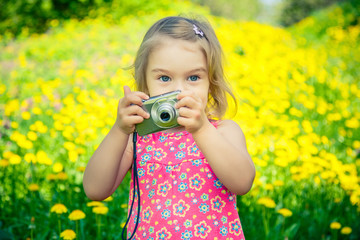 Little girl taking pictures on a meadow