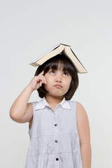 Portrait of little Asian child thinking and put a book on top