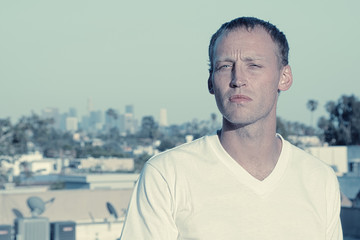 Serious Man in white T-shirt with Los Angeles sklyine
