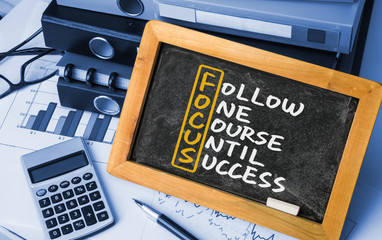 follow one course until success handwritten on blackboard