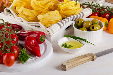 Italian food ingredients with pasta and fresh vegetables.