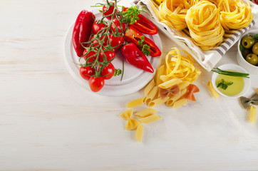 Italian food ingredients on a whiete wooden background.