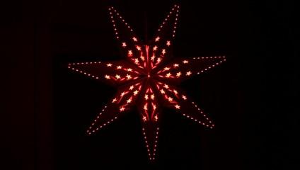 Rote Sterne leuchten vor schwarzem Hintergrund