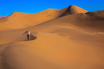 Woman is among sand dunes