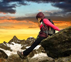 Girl sitting on rock in Swiss Alps, Europe