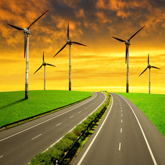 Empty Highway with wind turbines at sunset