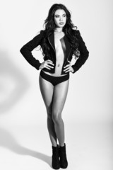 Hispanic woman wearing black jacket and panties on white backgro
