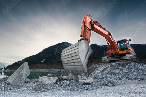 canvas print picture heavy organge excavator with shovel standing on hill with rocks