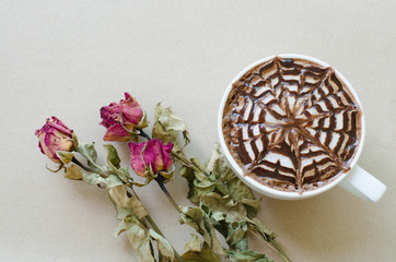 A cup of coffee with latte art and wither rose on brown paper ba
