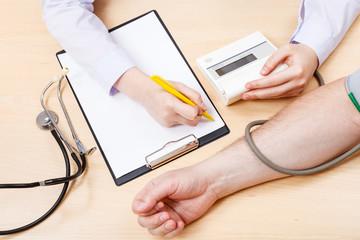nurse measures blood pressure of patient