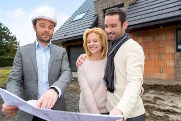 Real estate agent and a young couple in front of future home