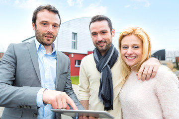 Real estate agent and a young couple in front of their next home