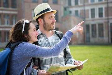 Couple of young attractive tourists watching map