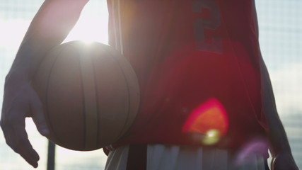 Basketball player holding ball with sun flare