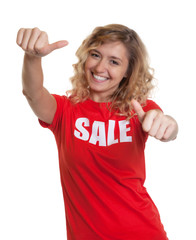 Blonde Frau im Sale-Shirt zeigt beide Daumen