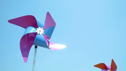 Colorful wind turbine rotating by blowing of wind,space for text