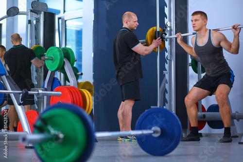 Tuinposter Gymnastiek Bodybuilder with barbell in gym