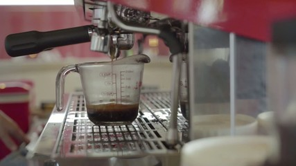 Fresh roasted coffee are being squeezed into a measuring cup