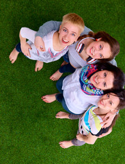 Four young women standing on green grass