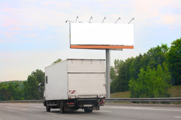 truck goes on highway by billboard