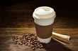 Paper cup of coffee and coffee beans on wooden table - 81430353