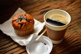 Paper cup of coffee and cake on wooden background