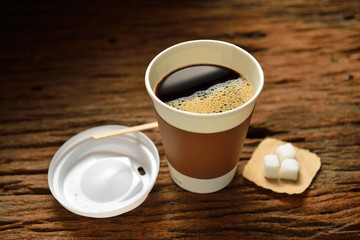Paper cup of coffee and sugar cube on wooden background