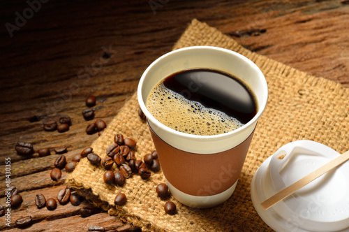 Fotobehang Koffie Paper cup of coffee and coffee beans on wooden table