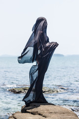 Female  silhouette wrapped in black fabric at the rocky seaside