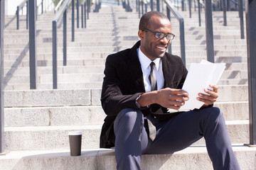 happy black businessman documents handling