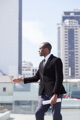 black businessman portrait on skyscrapers background