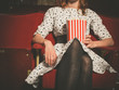 Young woman sitting in movie theater with popcorn - 81431305