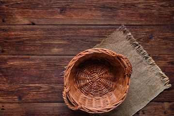 wooden table with basket on burlap texture background
