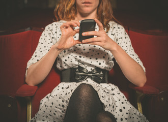 Young woman on front row of movie theater using her phone
