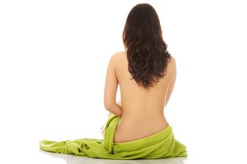 Woman in towel sitting on the floor.