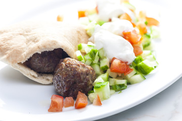 meatball in pan pita with tomato and cucumber salad