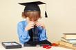 Little boy in academic hat looking through a microscope