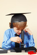 Little boy in academic hat studying something in a microscope