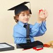 Little smiling boy in academic hat conducts scientific research