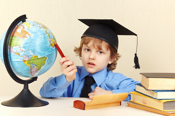 Little serious boy in academic hat with a pen showing on globe