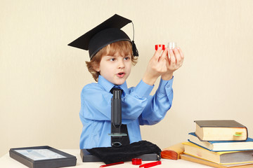 Little boy in academic hat conducts scientific research