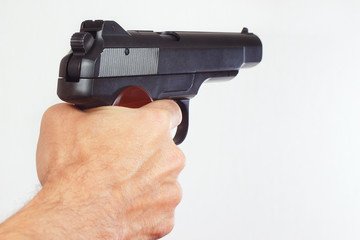 Hand with semi-automatic handgun close up