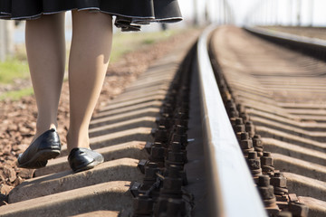 girl walking on the tracks in the spring