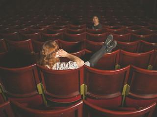 Woman on phone annoying man in auditorium