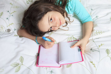 Girl writing diary in bed